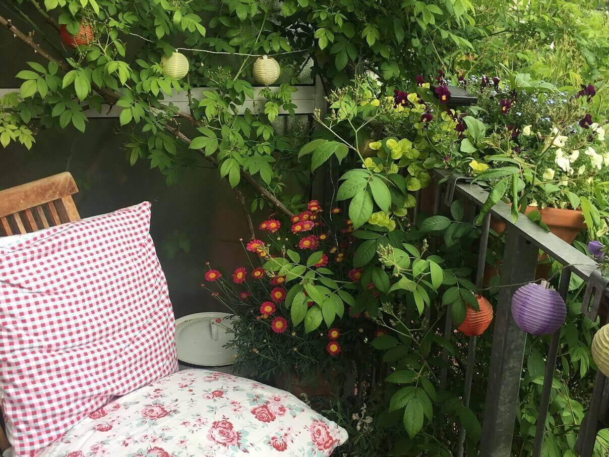 Stuhl und Lampions auf einem Balkon