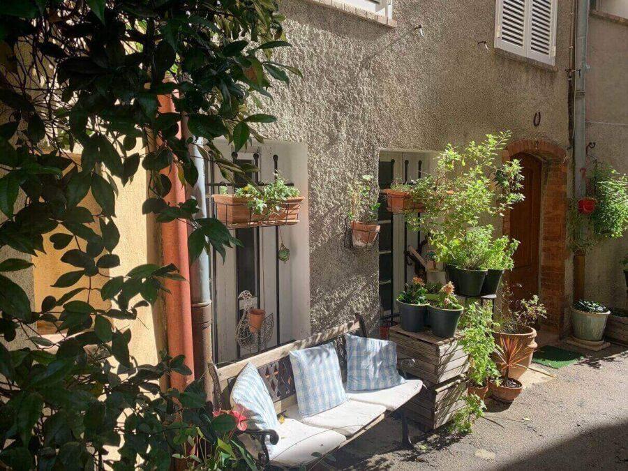 Bank und Pflanzenkübel vor einem Haus